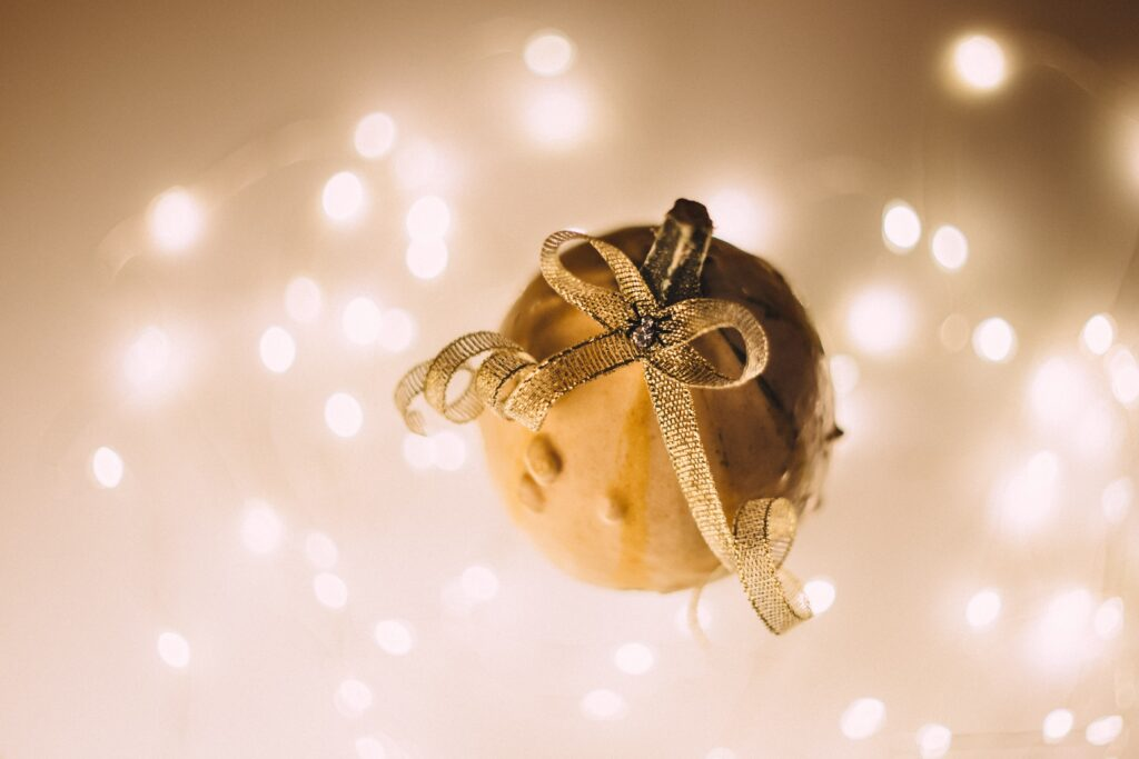 Holiday-themed team building questions section image with gold ornament and abstract lighting