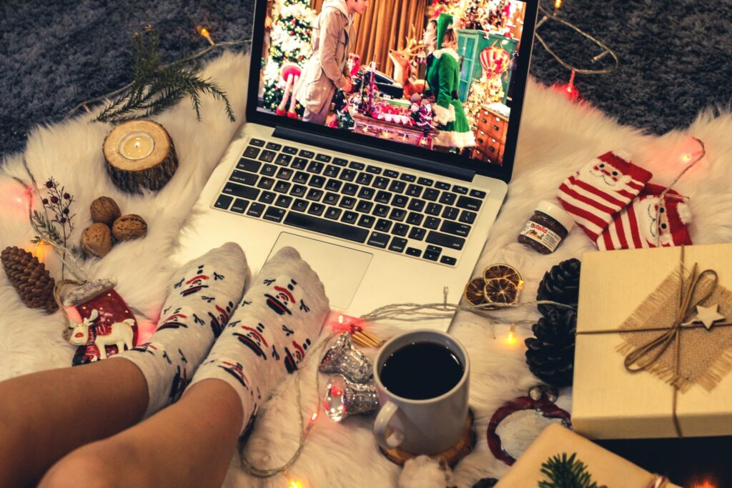 an employee watching a holiday movie on their laptop surrounded by decorations