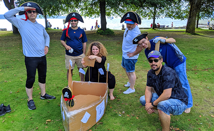 a team of colleagues doing a cardboard boat building challenge